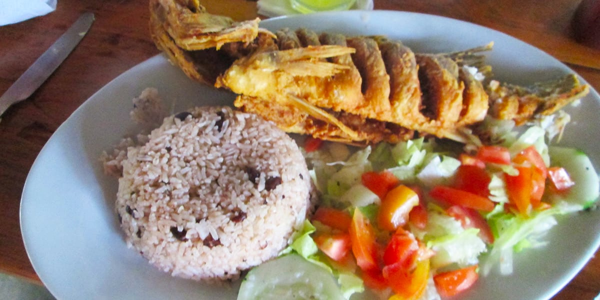 typical Panamanian meal fried corvina with arrows con wand and fresh salad
